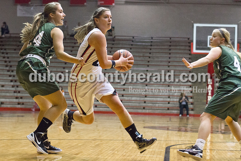 Rachel Mummey/The Herald<br /> Southridge's Kendyl Dearing flew past Forest Park's Libby Gress, left, and Amanda Jacob, right, during Monday night's game at Memorial Gym in Huntingburg. Southridge won 46-42.