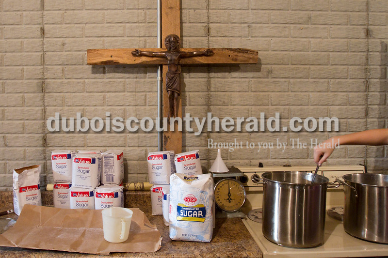 """Olivia Corya/The Herald<br /> St. Celestine and St. Raphael Catholic Cluster Churches parishioner Kelly Vonderheide of Celestine, 14, stirred a pot of sugar water as she helped concoct homemade wine for the church to use in communion in Deacon Mike Seibert's basement in Dubois on Saturday morning. This is the third year Seibert has hosted the wine making, and he says it's nice for parishioners to collaborate in the production because """"It builds a sense of community."""""""