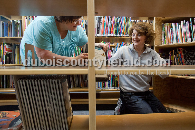 Rachel Mummey/The Herald<br /> Library page Lisa Streicher of Jasper, left, handed books to library assistant Lisa McWilliams of Huntinburg, right, as they packed up some of the library's 118,000 collection items at the Jasper Public Library on Monday. The Jasper Public Library is closed through Dec. 26 to allow the staff to install new shelving, tables and computer workstations, rearrange book sections, and add a new self-checkout station.