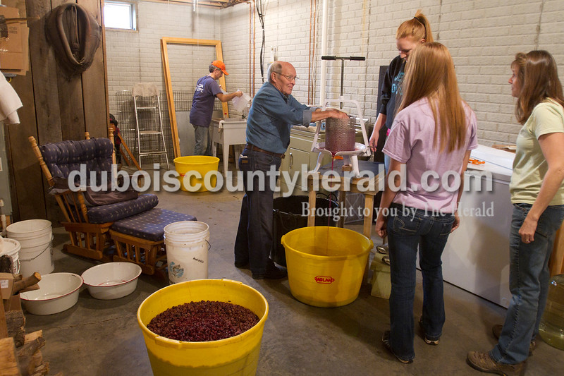 """Olivia Corya/The Herald<br /> St. Celestine and St. Raphael Catholic Cluster Churches parishioners Jack Goodman and Lori Vonderheide, both of Celestine, pressed the juice out of grapes while Lori's sister Kelly Vonderheide, 14, watched as they concocted homemade wine for the church to use in communion in the Dubois home of Deacon Mike Seibert, far back, and his wife Mary Seibert, far right, on Saturday morning. This is the third year Seibert has hosted the wine making, and he says it's nice for parishioners to collaborate in the production because """"It builds a sense of community."""""""