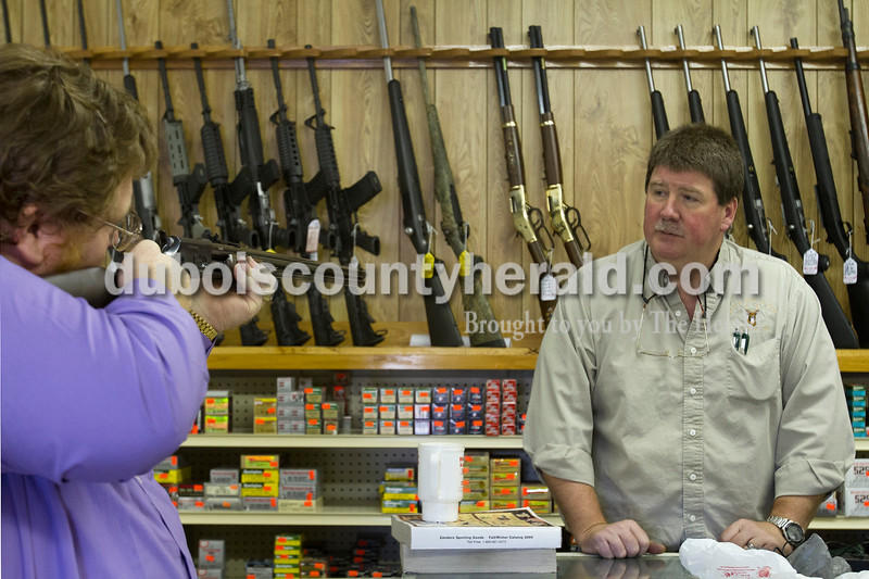 Olivia Corya/The Herald<br /> Jeff's Bait & Guns owner Jeff Miley of Jasper watched his frequent customer Andrew Bennington of Washington try out a Taurus C-45 long target rifle at the shop in Jasper on Wednesday. Local gun vendors have enjoyed a recent boost in sales. They attribute the uptick partly to the reelection of President Obama, whom many customers expect to tighten gun control legislation. This trend likely owes more to current gun owners purchasing additional firearms than it does to an increase in first time buyers; according to the General Social Survey conducted by the University of Chicago, the percentage of gun owning Americans has steadily declined for three decades.