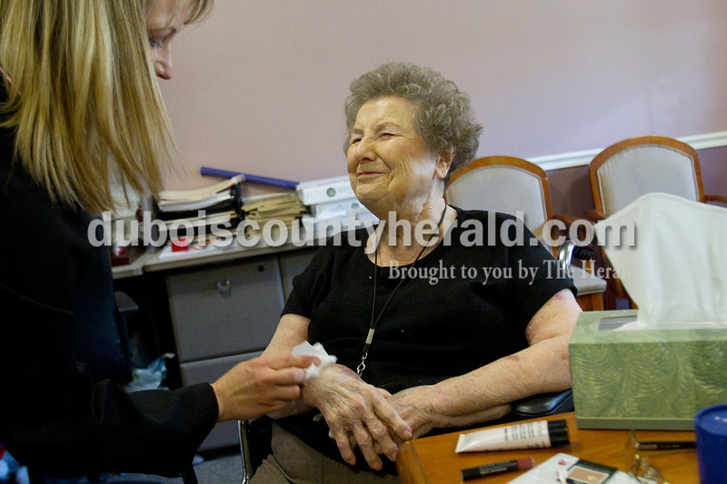 Olivia Corya/The Herald<br /> Brookside Village Senior Living Community resident Helen Bohnert had her arms moisturized as she received a complementary makeover from Mary Kay consultant Amy Knies of Jasper in celebration of Bohnert's 65th wedding anniversary with Charles Bohnert, also a Brookside resident, on Sunday morning. Later that day, friends and family came for a special open house in honor of the occasion. Helen said the star treatment made her feel very special.