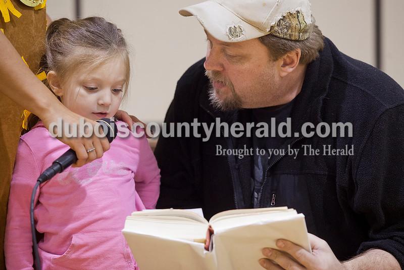 Rachel Mummey/The Herald<br /> Three-year-old Felecia Eckert of Birdseye got help reading aloud from Darrin Barnett of Huntingburg during the Dubois County Family Literacy Night at Huntingburg Elementary School on Tuesday.