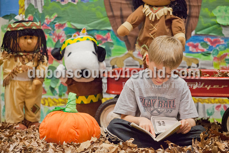 Rachel Mummey/The Herald<br /> Second-grader Cameron Tooley read Diary of a Whimpy Kid in the midst of a fall display during the Dubois County Family Literacy Night at Huntingburg Elementary School on Tuesday.
