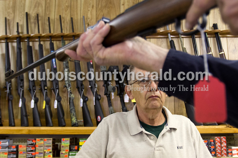Olivia Corya/The Herald<br /> Jeff's Bait & Guns employee Karl Vogts of Jasper watched a customer, who asked not to be identified, size up a C-Z .22 long target rifle he was considering buying in Jasper on Wednesday. Local gun vendors have enjoyed a recent boost in sales. They attribute the uptick partly to the reelection of President Obama, whom many customers expect to tighten gun control legislation. This trend likely owes more to current gun owners purchasing additional firearms than it does to an increase in first time buyers; according to the General Social Survey conducted by the University of Chicago, the percentage of gun owning Americans has steadily declined for three decades.