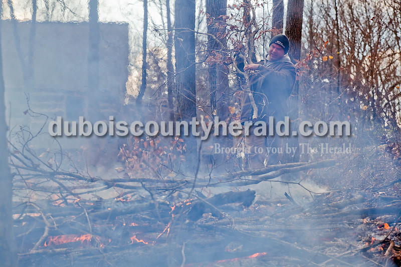 Rachel Mummey/The Herald<br /> Phil Buehler of Jasper tended to a brush pile he was burning in the woods in front of his home along 190 N on Friday afternoon. The day after Thanksgiving, he said he wanted to get outside and get some work done.