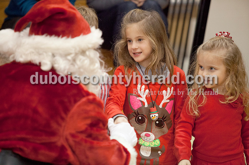 Rachel Mummey/The Herald<br /> Mickenzie Marks of Jasper, 5, and her cousin Emma Bauer of Jasper, 4, met Santa Claus at the American Legion Christmas Party at Jasper Middle School on Sunday.