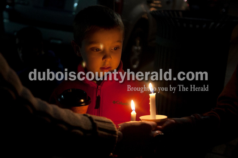 """Olivia Corya/The Herald<br /> Breckin Jochem of Huntingburg, 4, watched his mom Mara light his brother Aidan's candle before the the lighted Christmas parade began in Huntingburg on Fourth Street on Saturday. The parade featured Santa and Mrs. Claus, the Southridge Marching Band,  and afterward a """"Night at Bethlehem in the Marketplace"""" at Salem United Church of Christ."""