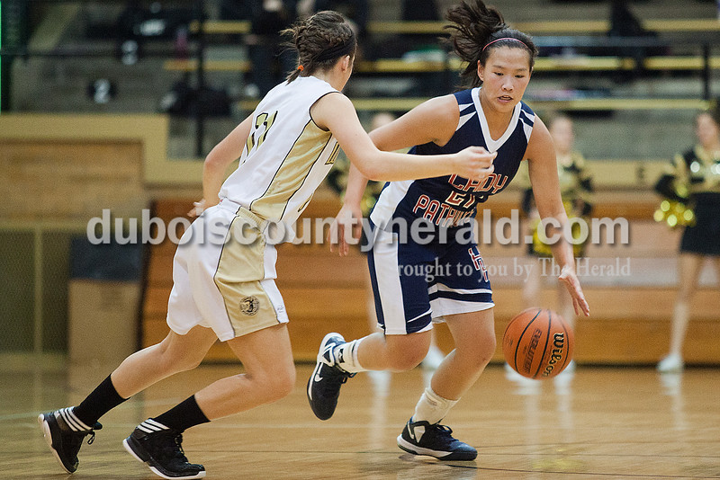 Rachel Mummey/The Herald<br /> Heritage Hills' Hayli Scott drove the ball down court while being guarded by Jasper's Emily Jones during Monday night's game against Heritage Hills at Cabby O'Neill Gym in Jasper.