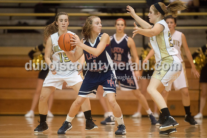 Rachel Mummey/The Herald<br /> Heritage Hills' Paige Priest pivoted between Jasper's Allyson Lents, left, and Tori Sermersheim, right, during Monday night's game at Cabby O'Neill Gym in Jasper.