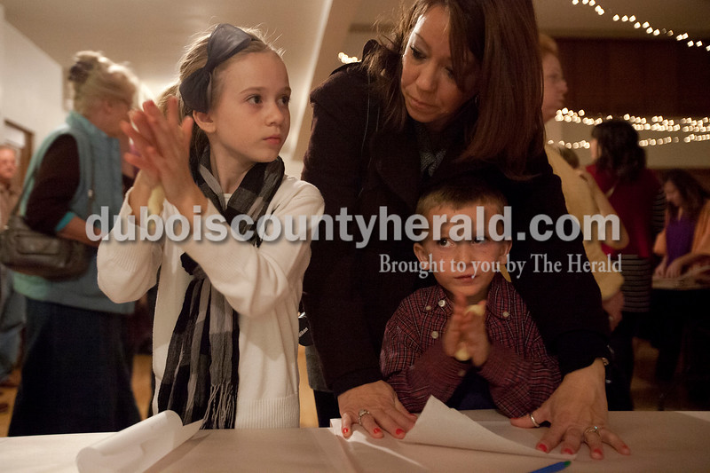 """Olivia Corya/The Herald<br /> Montanna Yother of Huntingburg, 8, and her brother Blake, 6, rolled dough before shaping it into a pretzel while their mom Shellie watched inside Salem United Church of Christ on Saturday evening. The inside of the church was transformed into """"Bethlehem at the Marketplace,"""" complete with costumed volunteers and Bethlehem themed activities for children. Pretzels were part of the occasion, according to volunteers, because they are modeled after the shape of praying hands."""