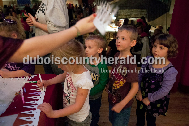 """Olivia Corya/The Herald<br /> Mya Menke of Holland, 5, decorated a paper crown while Aiden Wiscaver of Petersburg, 3, second to left, his brother Layton Wiscover, 5, and their cousin Gracelyn Miller of Petersburg, 4, awaited their turn inside Salem United Church of Christ on Saturday evening. The inside of the church was transformed into """"Bethlehem at the Marketplace,"""" complete with costumed volunteers and Bethlehem themed activities for children. The crowns were part of the festivities because they represented King Harod."""