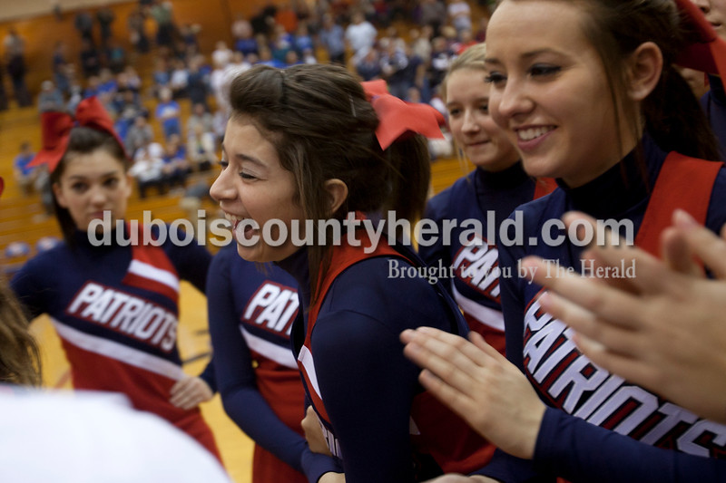 Olivia Corya/The Herald<br /> Heritage Hills sophomores Salina Wilkerson, center, and Lauren Hohl laughed as they received cheering instructions from their coach before Saturday night's basketball game against Northeast Dubois at Heritage Hills. The Patriots defeated the Jeeps 68-66.
