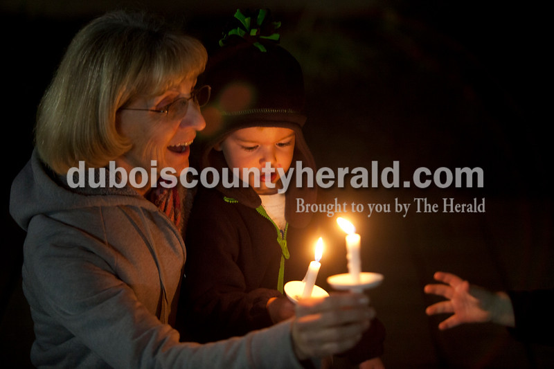 """Olivia Corya/The Herald<br /> Connie Kissling of Huntingburg smiled at her grandson Ryley Messmer, 1, as he reached for the candle her other grandson Wyatt Messmer of Huntingburg, 3, was holding as they waited for the lighted Christmas parade in Huntingburg to begin on Fourth Street on Saturday. The parade featured Santa and Mrs. Claus, the Southridge Marching Band,  and afterward a """"Night at Bethlehem in the Marketplace"""" at Salem United Church of Christ."""