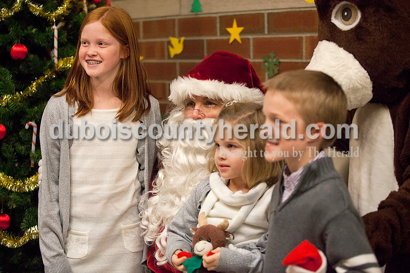 Rachel Mummey/The Herald<br /> Abby Gubbins of Jasper, 10, and her siblings Sophie, 5, and Will, 8, posed for a photo with Santa Claus at the American Legion Christmas Party at Jasper Middle School on Sunday.