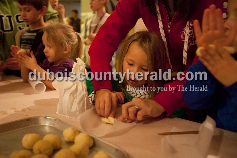 """Olivia Corya/The Herald<br /> Rachel Wright of Huntingburg helped her daughter Madalyn, 3, fold dough into a pretzel inside Salem United Church of Christ on Saturday evening. The inside of the church was transformed into """"Bethlehem at the Marketplace,"""" complete with costumed volunteers and Bethlehem themed activities for children. Pretzels were part of the occasion, according to volunteers, because they are modeled after the shape of praying hands."""