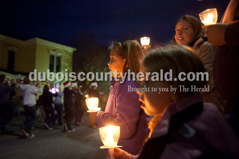 """Olivia Corya/The Herald<br /> Katelyn Hassfurther of Ferdinand, 8, left, watched the lighted Christmas parade approach with her sister Rachel, 6, and mom Amanda in Huntingburg on Fourth Street on Saturday. The parade featured Santa and Mrs. Claus, the Southridge Marching Band,  and afterward a """"Night at Bethlehem in the Marketplace"""" at Salem United Church of Christ."""