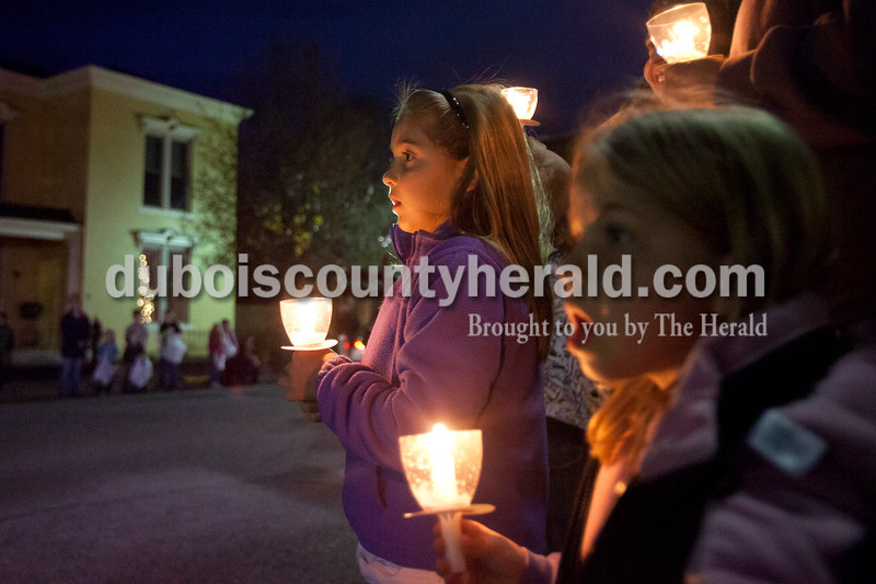 """Olivia Corya/The Herald<br /> Katelyn Hassfurther of Ferdinand, 8, left, watched the lighted Christmas parade approach with her sister Rachel, 6, in Huntingburg on Fourth Street on Saturday. The parade featured Santa and Mrs. Claus, the Southridge Marching Band,  and afterward a """"Night at Bethlehem in the Marketplace"""" at Salem United Church of Christ."""