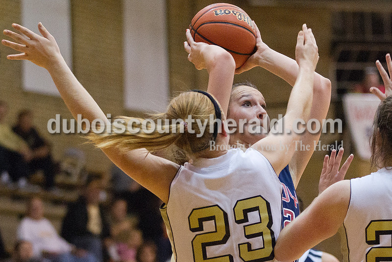 Rachel Mummey/The Herald<br /> Heritage Hills' Maddie Fella went up for a shot while being blocked by Jasper's Tori Sermersheim during Monday night's game at Cabby O'Neill Gym in Jasper.
