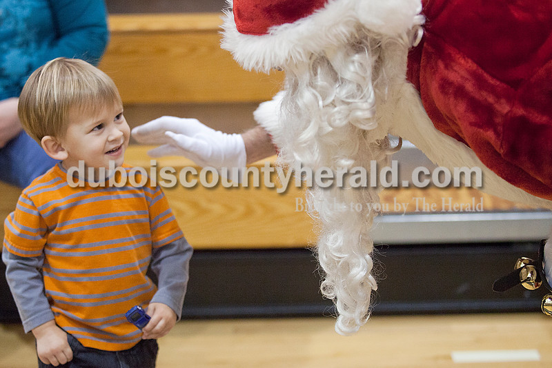 Rachel Mummey/The Herald<br /> Tristan Castillo of Huntingburg, 2, was greeted by Santa Claus at the American Legion Christmas Party at Jasper Middle School on Sunday.