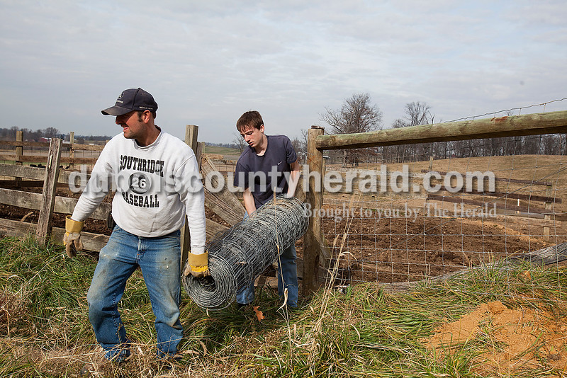 Rachel Mummey/The Herald<br /> Brian Lammers of Huntingburg, and his son Justin, 13, carried a bundle of woven wire back to the barn after rebuilding a section of fence where they keep cattle along Hwy 64 in Huntingburg on Saturday. Brian said he was working with his son so he'd gain the experience of fence building.