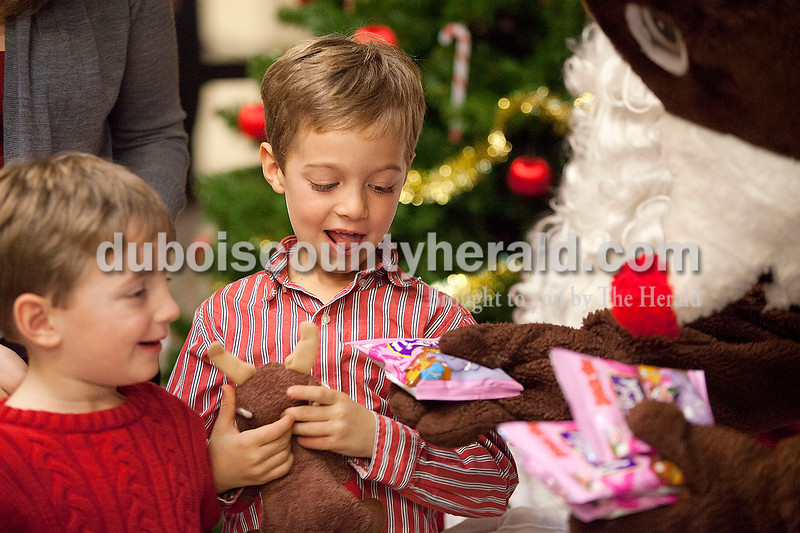 Rachel Mummey/The Herald<br /> Carson Bauer of Jasper, 6, center, and his brother Ethan, 4, left, received treats from Santa Claus at the American Legion Christmas Party at Jasper Middle School on Sunday.
