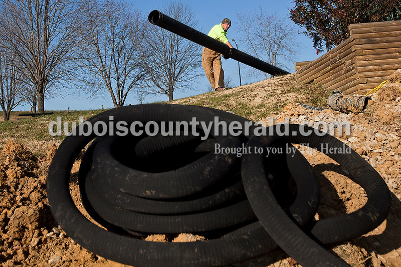 Dave Weatherwax/The Herald<br /> Colin Leinenbach, an employee of the parks department for the City of Huntingburg, carried a long piece of storm drain as he worked on replacing a drainage system around the perimeter of the baseball field at Southside Park in Huntingburg last Thursday morning. The project is one of many related to the baseball field that parks department employees are busy with during the winter months as long as the weather cooperates. When the weather does pose issues, Dale Payne, the park maintenance foreman for the city, said they have plenty of projects to work on indoors.