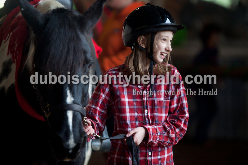 "Olivia Corya/The Herald<br /> Emily Merkley of Dubois, 10, waited for the next rider to mount the horse she was leading around a barn decorated as ""candy cane lane""  during Christmas for St. Jude, a fundraiser for the children's hospital, at Briar Bush Farm in Celestine on Saturday. The event, which also featured a petting zoo and finger painting a real horse, was organized by Luckie Hopf and took place on her sister Ruth Bush's property. Emily is a riding student at the farm."