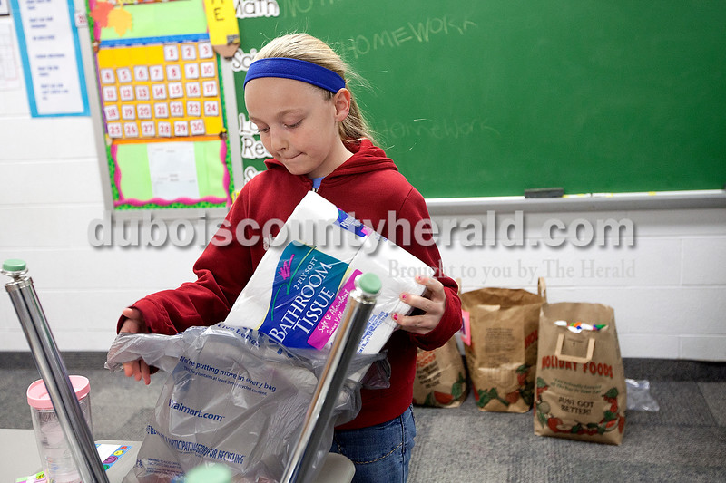 Dubois Elementary School fourth-grader Payton Bowles unpacked some items to put inside her class' Build-A-Basket box the morning of Nov. 30. The Build-A-Basket project is sponsored by AngelWorx and aims to collect items such as dish soap, deodaorant and toopaste to put in plastic laundry baskets forhomebound individuals.