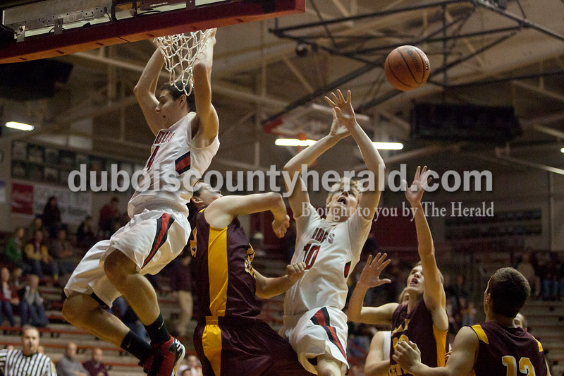 Olivia Corya/The Herald<br /> Southridge's Chad O'Bryan reached for the rebound after his teammate Cody Thompson attempted a slam dunk during Saturday night's game against Pike Central at Huntingburg Memorial Gym. The Raiders defeated the Chargers 60-36.