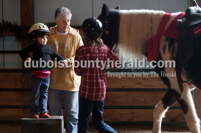 Olivia Corya/The Herald<br /> Liza Poppe of Jasper, 3, prepared to mount a horse led by Emily Merkley of Dubois, 10, with her grandmother Luckie Hopf's help during Christmas for St. Jude, a fundraiser for the children's hospital, at Briar Bush Farm in Celestine on Saturday. The event, which also featured a petting zoo and finger painting a real horse, was organized by Hopf and took place on her sister Ruth Bush's property. Emily is a riding student at the farm.