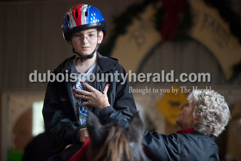 Olivia Corya/The Herald<br /> Ruth Bush of Celestine helped Josh Braunecker of Huntingburg, 11, relax as he rode a horse during Christmas for St. Jude, a fundraiser for the children's hospital, at Briar Bush Farm in Celestine on Saturday. The event, which also featured a petting zoo and finger painting a real horse, took place on Bush's property and was organized by her sister Luckie Hopf. During his first lap around the barn, Josh had been really tense and this in turn made the horse tense, so Bush had him straighten his posture to help him take big calming breaths.