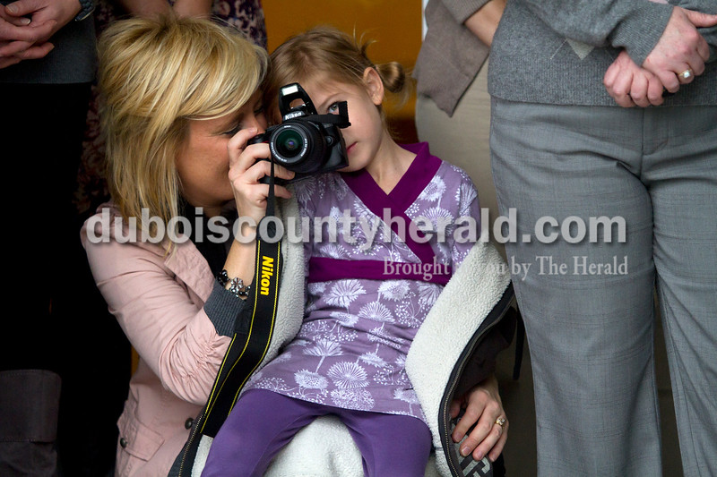 Olivia Corya/The Herald<br /> Kara Kurrucz, 8, looked through the viewfinder of Ashley Werner's camera during the dedication ceremony of St. Thomas Medical Center, Jasper's newest medical facility, on Saturday. The center includes the orthopedic office of Dr. Daniel Eby, Memorial Hospital's Outpatient Surgery Center and MRI Suite, and a chapel. Kara's father is a doctor at the center, and Werner is employed there as a scheduler.