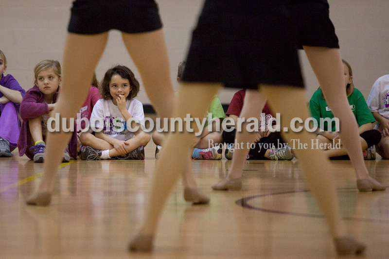 Olivia Corya/The Herald<br /> Emma Zoglman, 7, far left, and Mallory Krapf, 7, both of Jasper, watched Jasper Dance Team members demonstrate a routine during a dance clinic at Jasper High School on Saturday. During the clinic, which was a fundraiser for the dance team, participants learned moves to both a hip hop and Christmas song, which they later performed during half time at that night's Jasper versus Bedford basketball game.