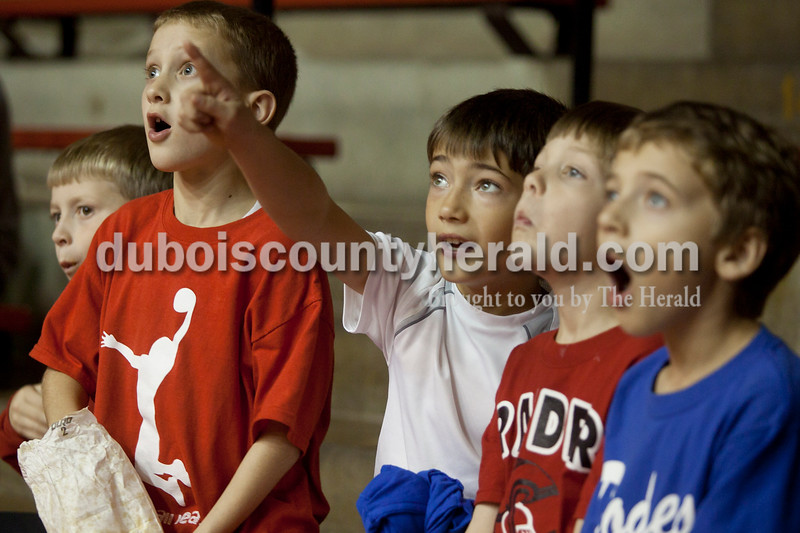 Olivia Corya/The Herald<br /> Kaden Thyen, 8, pointed out a set of speakers that was hanging from the ceiling and swaying back and forth to his friends Cameron Allen, 8, far left, Cole Wirthwein, 8, Owen Morrison, 7, and his twin brother Kyan Thyen, far right, during Saturday night's basketball game against Pike Central at Huntingburg Memorial Gym. The boys, all of Huntingburg, suspected the wires holding the speakers were going to snap, and throughout the game they kept an eye on it.