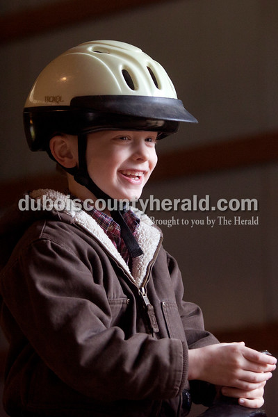 Olivia Corya/The Herald<br /> Andy Merkley of Dubois, 5, beamed as he rode a horse around a holiday decorated barn as part of Christmas for St. Jude, a fundraiser for the children's hospital, at Briar Bush Farm in Celestine on Saturday. The event, which also featured a petting zoo and finger painting a real horse, was organized by Luckie Hopf and took place on her sister Ruth Bush's property. Andy's older sister Emily takes riding lessons at the farm, and he hopes to one day join her.