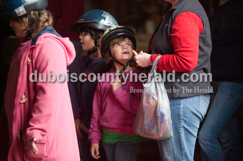 Olivia Corya/The Herald<br /> Lorelei Poppe of Jasper, 6, told Stacie Gilles of Jasper which was her favorite horse as she stood next to her sister Magdalene, 8, second to left, and Gilles' daughter Peyton, 9, as they waited in line to ride horses  during Christmas for St. Jude, a fundraiser for the children's hospital, at Briar Bush Farm in Celestine on Saturday. The event was organized by the Poppes' grandmother Luckie Hopf and took place on their great aunt Ruth Bush's property.