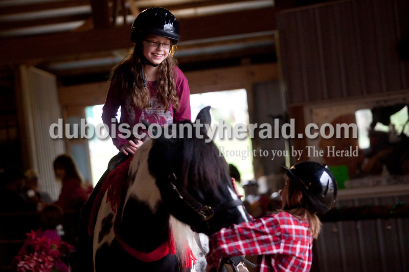 Olivia Corya/The Herald<br /> Devon Lehmkuhler of Princeton, 12, was led by fellow riding student Emily Merkley of Dubois, 10, as she rode a horse around a holiday decked barn as part of Christmas for St. Jude, a fundraiser for the children's hospital, at Briar Bush Farm in Celestine on Saturday. The event, which also featured a petting zoo and finger painting a real horse, was organized by Luckie Hopf and took place on her sister Ruth Bush's property.