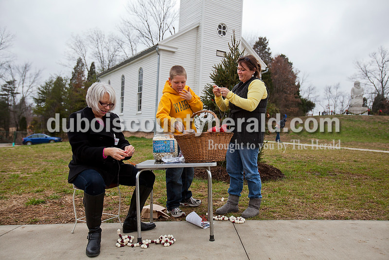 Rachel Mummey/The Herald<br /> Santa Claus Museum & Villiage volunteer Barb Blair of Santa Claus, left, was joined by Elijah Burns of Jeffersonville, 10 and his mother Jessica, in making garland from cheese balls and cranberries during the first annual Merry Little Christmas celebration in Santa Claus on Saturday.