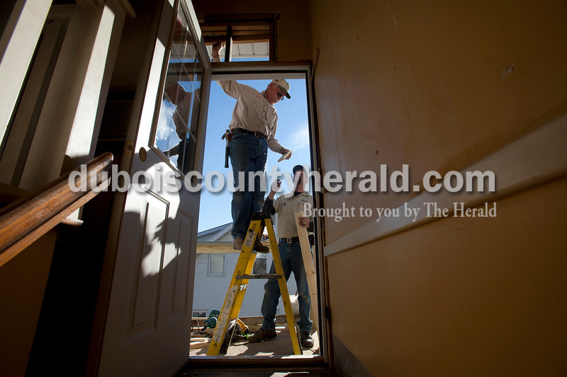 "Olivia Corya/The Herald<br /> Sylvester ""Nessy"" Hassfurther, left, and Steve Fischer, both of Ferdinand, installed a new exterior door leading to a patio and stairs they recently built for a client in Jasper on Thursday. Fischer owns Dubois County House Works and Hassfurther is his employee."