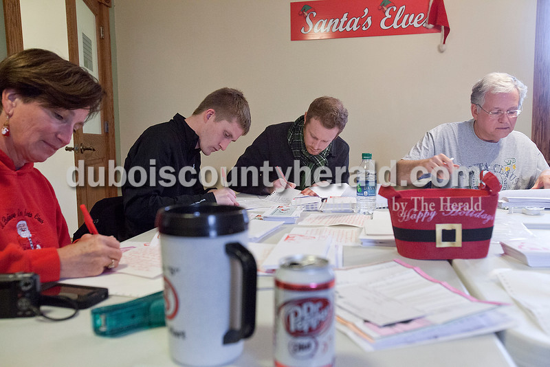 Rachel Mummey/The Herald<br /> Helper elves Kathy Kamp of Santa Claus, left, Alex Bruner of Evansville, Justin Schuring of Evansville and Daryl Lovell of Dale wrote tirelessly to respond to countless letters to Santa that have arrived from around the globe to Santa Claus on Saturday. The letters have requested everything from money and toys, to food and the return of parents from overseas.