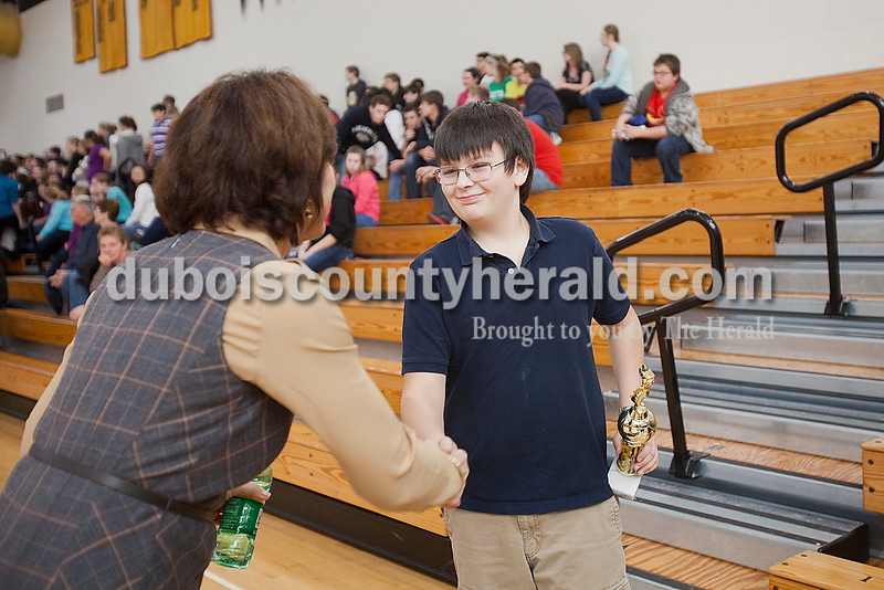 Rachel Mummey/The Herald<br /> Jasper Middle School eighth-grader Aidan Kay received a congratulatory handshake from eighth-grade social studies teacher Lisa Seng after Kay won the geography bee for the second year in a row on Friday.