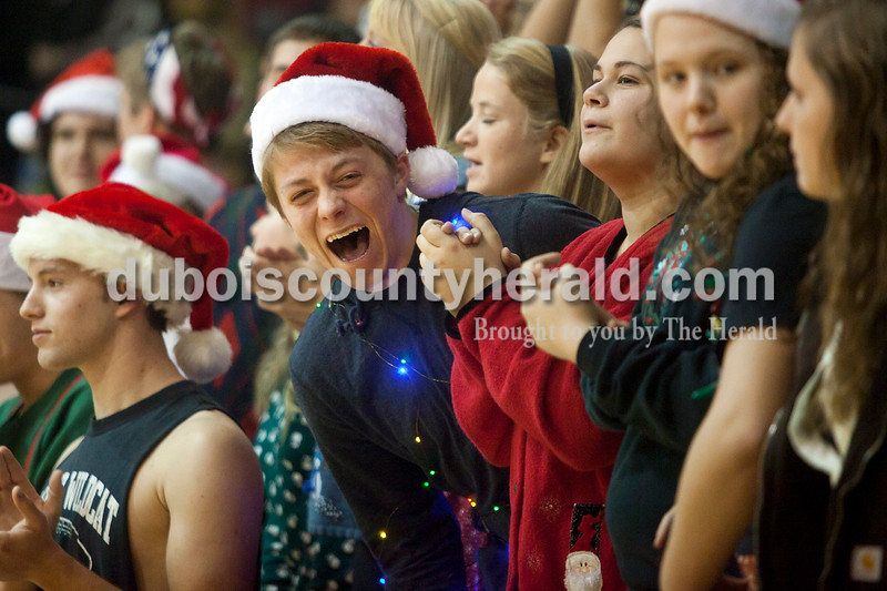 Olivia Corya/The Herald<br /> Jasper senior Kade Elliott cracked up as he saw a friend's elaborate elf costume while himself wearing holiday lights for the student section's Christmas theme before Saturday night's basketball game against Southridge at Cabby O'Neill Gymnasium in Jasper.