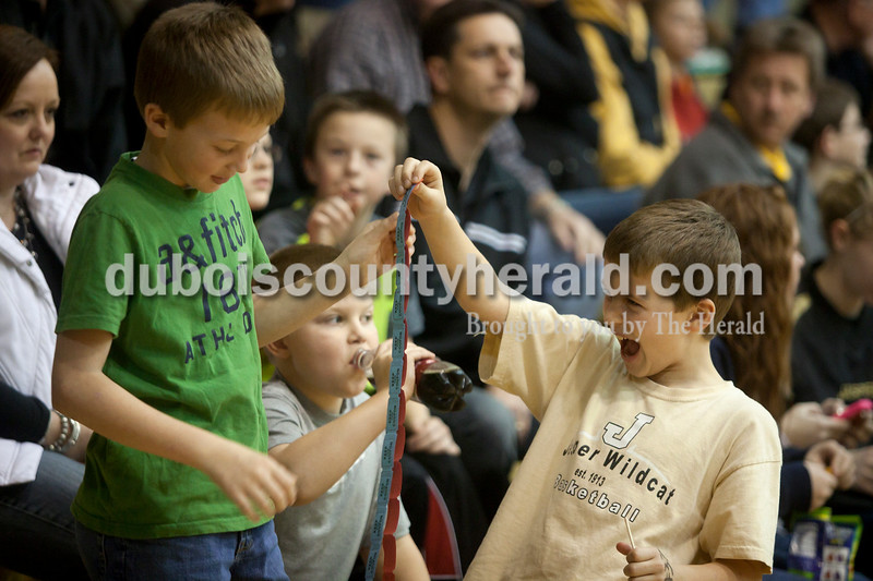 Olivia Corya/The Herald<br /> Jack Ahlbrand, 8, right, smiled as he realized he had more raffle tickets than his friend Jobe Luebbehusen, 9, as they waited for Saturday night's Jasper versus Southridge basketball game to begin at Cabby O'Neill Gymnasium in Jasper. The tickets were for a raffle to compete in a half court challenge, for which Jack said his dad, who coaches for Jasper, has been helping him practice. Both boys are from Jasper.