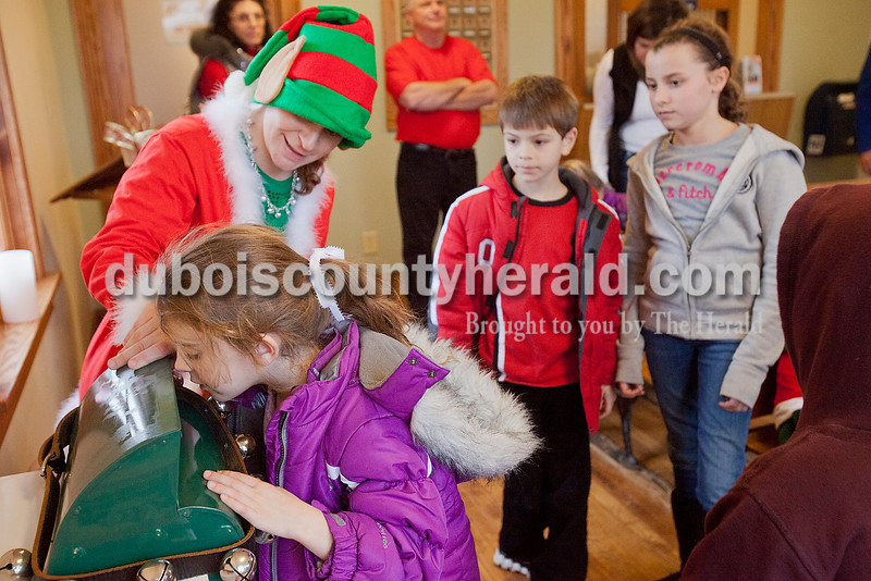 Rachel Mummey/The Herald<br /> Sophia Towle of Columbus, Ohio, 8, watched as she slipped her letter to Santa into the dropbox with help from Holly the Elf at the Original Santa Claus Post Office during its grand opening on Saturday. She was there with members of her family including her step-brother Quinten Rubcich, 8, second from right, and cousin Ava Towle, 11, far right.