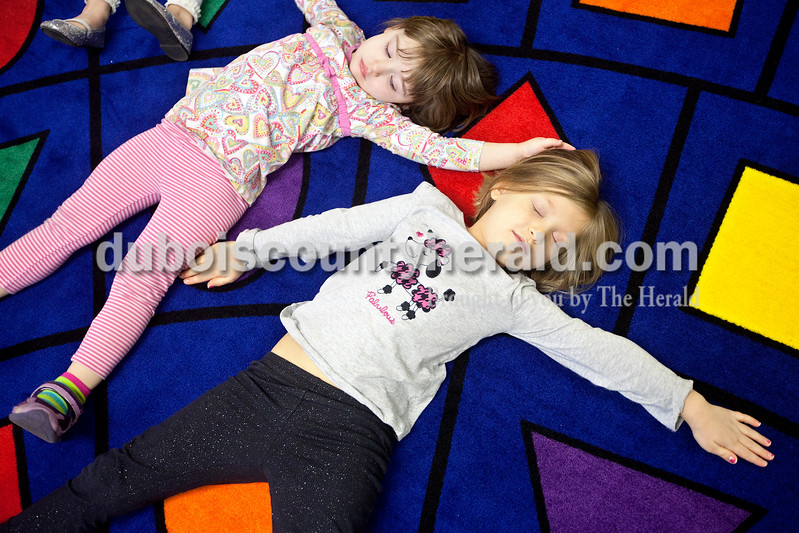 Dave Weatherwax/The Herald<br /> Jaelyn Buehler, 3, left, and Olivia Rasche, 4, both of Huntingburg, pretended to make snow angels on the ground during Story Hours at the Huntingburg Public Library on Monday.