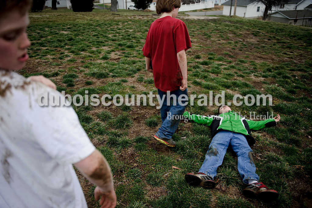 Matthew Busch/The Herald<br /> Quentin Lechner, 11, right, laid down exhausted after a football play as Andrew Franklin, 10, second right, walked over to him during a game of football outside Franklin's home after school in Jasper on Tuesday. Dayton Shelton, 11, left, looked at the mud on his t-shirt after the play as well. The three friends are from Jasper and all attend 10th street elementary.