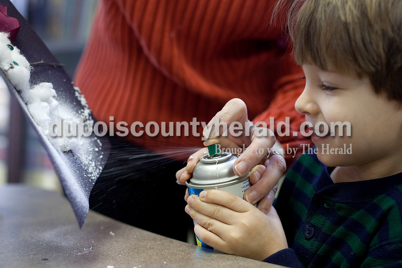 Dave Weatherwax/The Herald<br /> Eli Englert of Huntingburg, 4, received help from the children's librarian Lynn Hensley at the Huntingburg Public Library in spraying fake snow on his snowman craft Monday morning.