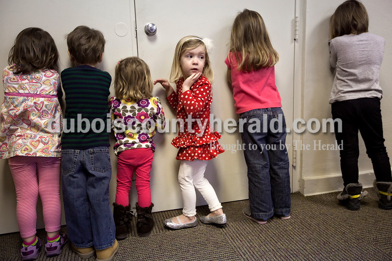 """Dave Weatherwax/The Herald<br /> Lila Hawkes of Jasper, 3, fourth from left, snuck a quick peak as a small pig was being hidden by another child while playing """"hide-the-pig"""" at the Huntingburg Public Library on Monday morning. The game was part of Story Hours, which consisted of stories, games and crafts for children ages, 3, 4 and 5. The children also had the chance to make snowmen out of cotton balls during the first session of the spring series. The sessions take place on Mondays from 10 a.m. to 11 a.m. and from 1 to 2 p.m. Thursdays. They will run through the week of March 14."""