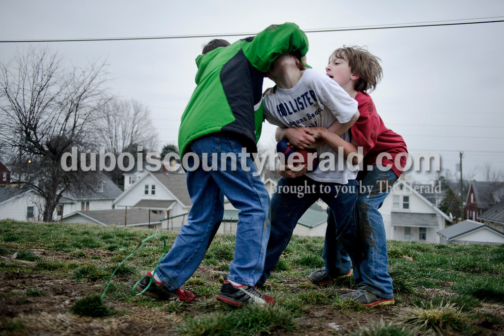 Matthew Busch/The Herald<br /> Quentin Lechner, 11, and Andrew Franklin, 10, right, tackled Dayton Shelton, 11, center, during a football game outside of Franklin's house after school in Jasper on Tuesday. The three friends are from Jasper and all attend 10th street elementary.